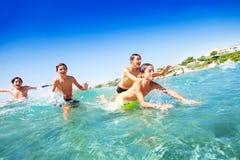 Vier glückliche Teenager, die im Meer schwimmen lizenzfreie stockfotografie