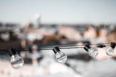 Vier Glasbirnen gegen die Dächer von Häusern und von Himmel Die Birne auf die Oberseite Die Ansicht von der Oberseite Abschluss o stockfotos