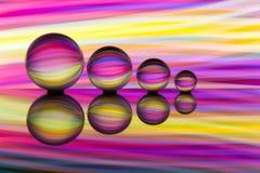 Vier Glaskugeln in Folge mit bunten Streifen der Regenbogenfarbe hinter ihnen stockfotografie