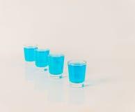 Vier glazen van blauwe kamikaze, betoverende drank, gemengde drank gieten Stock Foto
