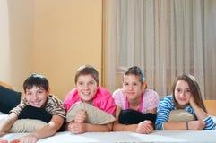 Vier glückliche Jugendfreunde, die auf dem Bett liegen Stockbild