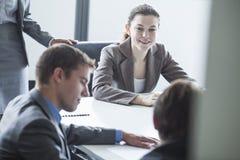 Vier glimlachende bedrijfsmensen die bij een lijst zitten en een commerciële vergadering in het bureau hebben Stock Fotografie