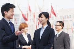 Vier glimlachende bedrijfsmensen die in openlucht in Peking, China spreken Royalty-vrije Stock Afbeeldingen