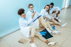 Vier glimlachende jonge medische internen die in witte robes op een vloer in het ziekenhuis hoog-fiving zitten royalty-vrije stock foto's