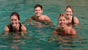 Vier glimlachende mensen die wateraerobics in zwembad doen stock footage