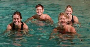 Vier glimlachende mensen die wateraerobics in zwembad doen stock videobeelden