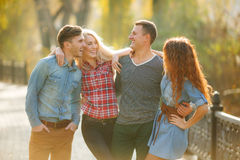 Vier goede vrienden ontspannen en hebben pret in de herfstpark Stock Fotografie