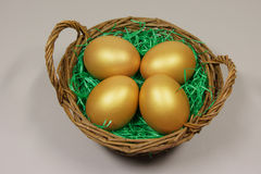 Vier gouden eieren in mand Stock Fotografie