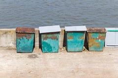 Vier (4) grüne Abfallbehälter, die auf dem Stein-embankme stehen Lizenzfreie Stockbilder
