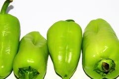 Vier grüne Gemüsepaprikas auf weißem Hintergrund stockbilder