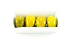 Vier grüne Oliven in einem Teller Stockbilder