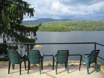Vier grüne Stühle, die einen See übersehen Lizenzfreies Stockfoto