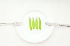 Vier groene erwten in bonen op whuteplaat Royalty-vrije Stock Afbeeldingen