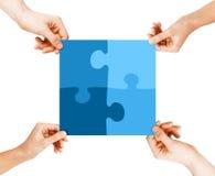 Vier Hände, die Puzzlespielstücke anschließen Lizenzfreie Stockfotografie