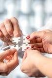 Vier Hände, die zusammen zusammenpassende Ineinander greifenpuzzlespielstücke passen Lizenzfreies Stockfoto