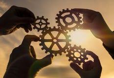 Vier Hände sammeln den Gang von den Gängen der Details der Puzzlespiele Lizenzfreie Stockfotos