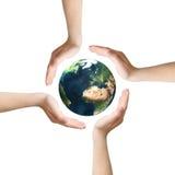Vier Hände um Erde Stockbild