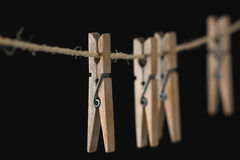 Vier hölzerne Wäscheklammern auf einem Draht Stockfotografie