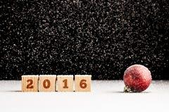 Vier hölzerne Würfel mit Zeichen 2016 auf ihnen legend auf schneebedeckte Oberfläche Stockfotografie
