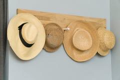 Vier Hüte, die in einer hölzernen Wand hängen Stockbild