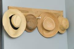 Vier Hüte, die in einer hölzernen Wand hängen Stockbilder