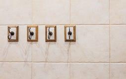 Vier haken op badkamersmuur stock afbeelding
