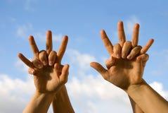 Vier handen het toejuichen Stock Afbeelding