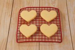 Vier hart gevormd die koekje bij het koelen van dienblad wordt gehouden royalty-vrije stock fotografie