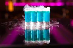 Vier hellblaue Cocktailschüsse mit Rauche auf reflektierender Spiegeltabelle stockbild