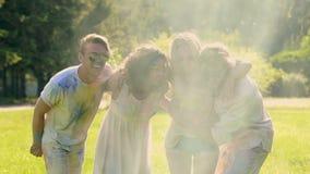 Vier het gelukkige vrienden springen behandeld in kleurrijk poeder, traditioneel holifestival stock videobeelden
