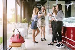 Vier het winkelen meisjesbespreking en lach, in de wandelgalerij Royalty-vrije Stock Afbeeldingen
