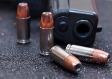 Vier hohle Punktkugeln mit einer schwarzen Pistole Lizenzfreie Stockfotografie