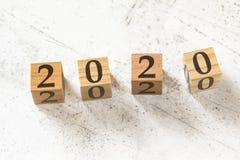Vier houten kubussen met nummer 2020 op witte werkende raad royalty-vrije stock foto's