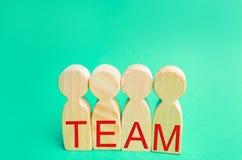 vier houten mensen met het inschrijvings` team ` Het groepswerk groepswerk voltooiing van doelstellingen, collectieve geest samen stock foto
