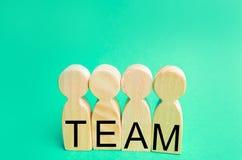 vier houten mensen met het inschrijvings` team ` Het groepswerk groepswerk voltooiing van doelstellingen, collectieve geest samen stock foto's