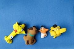 Vier Hunde vom Plasticine auf einem blauen Hintergrund Stockbilder