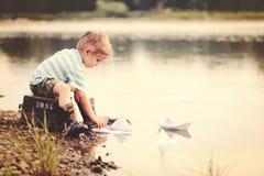 Vier jaar het oude blonde jongen spelen met document boten op het water stock foto