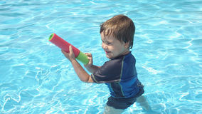 Vier jaar het oude jong geitje spelen in het zwembad Stock Foto