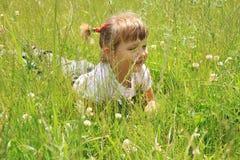 Vier jaar oud meisjes ligt in het gras Royalty-vrije Stock Afbeeldingen