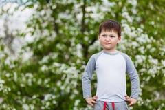 Vier-jaar-oude kindtribunes op de achtergrond van witte Apple-bloemen stock foto