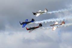 Vier jak-52 trainervliegtuigen in vorming, slepende rook royalty-vrije stock afbeeldingen