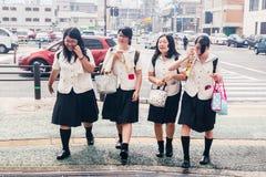 Vier Japanse Schoolmeisjes die de straat kruisen Hitte in de stad stock foto's