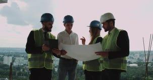 Vier jong ingenieurs en architectenteam die het project van de bouw analyseren stock videobeelden