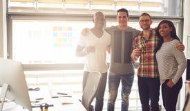 Vier jonge en gelukkige volwassenen in bureau Stock Foto