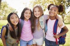 Vier jonge glimlachende schoolmeisjes op een schoolreis royalty-vrije stock afbeelding