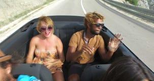 Vier jonge hipstervrienden die pret het berijden in convertibel hebben stock videobeelden