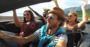 Vier jonge hipstervrienden die pret het berijden in convertibel hebben stock footage