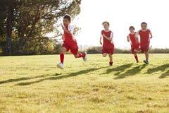 Vier jonge jongens in voetbalstrook die op een speelgebied lopen stock foto