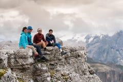 Vier jonge mannelijke en vrouwelijke wandelaars die op een berg zitten bereiken richel in het Dolomiet en het bekijken de verbaze royalty-vrije stock afbeeldingen