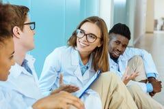 Vier jonge medische internen die op vloer in het ziekenhuisgang zitten, het glimlachen royalty-vrije stock foto